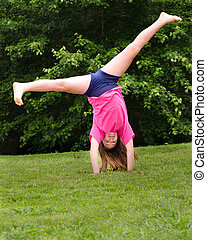 Young girl doing a cartwheel outdoors at park