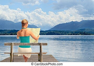 Woman with map on a lake
