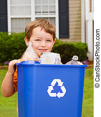 Recycling concept with young child carrying recycling bin to the curb at his house