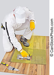 Worker applies tile adhesive on wooden floor with reinforcement