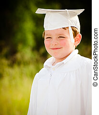 Young boy with cap and gown for preschool graduation
