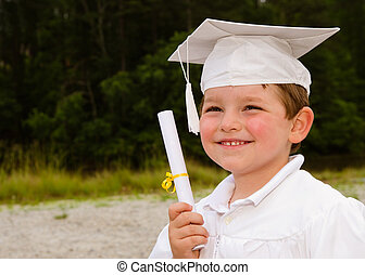 Young boy with cap and gown and certificate for preschool...