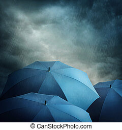 Dark clouds and umbrellas - Dark stormy clouds and umbrellas