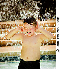 Child playing under waterfall at pool
