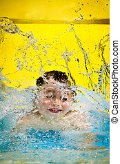 Young boy or kid has fun splashing into pool after going...