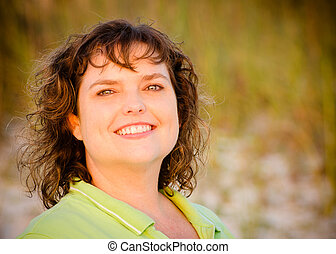 Portrait of happy middle-aged woman at beach with sand dunes...