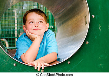 Cute young child boy or kid playing in tunnel on playground