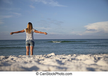 Relaxed Beach Woman - A woman feels the breeze from the...