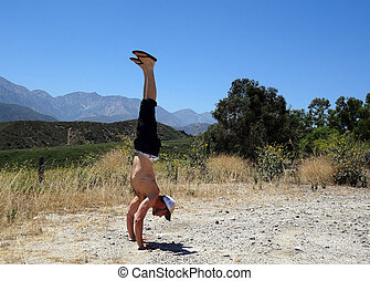 Handstanding in Dirt Field in California with Mountain in...