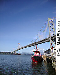 Fireboat docked in front of the San Francisco-Oakland Bay Bridge looking towards the east bay on a nice day