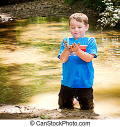Child playing in mud in forest creek