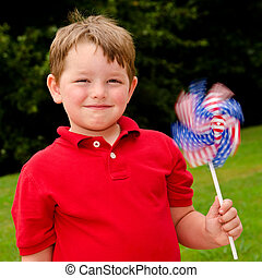 Child playing with American flag pinwheel to celebrate...