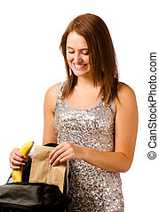 Teen girl packing healthy lunch for school isolated on white