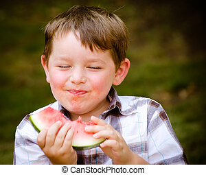 Summer portrait of cute young child eating watermelon...