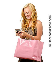 Portrait of teen girl with pink shopping bag texting with...