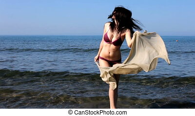 Beautiful girl playing on the beach - female model wearing...