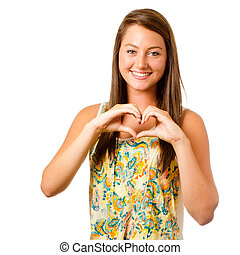 Smiling teenager girl making heart shape with her hands...