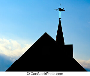 Silhouette of roof of historic building with weather vane in...