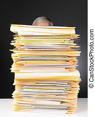 Businessman Behind Stack of Files - An overworked...