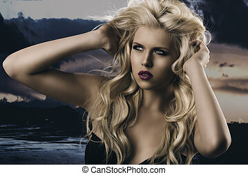 beauty portrait of blonde girl with hands in the hair