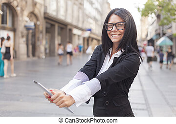 Businesswoman on street holding tablet computer