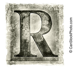 R - Textured image of a metallic letter R.