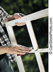 Fixing the windows. - Man using a piece of abrasive...