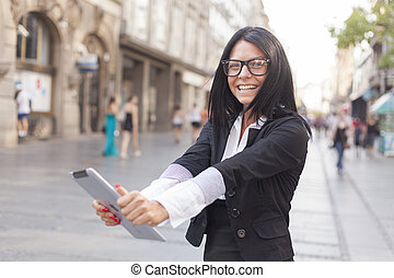 Businesswoman on street with tablet computer