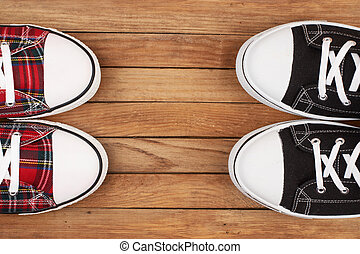 Two pairs of sneakers on wooden background