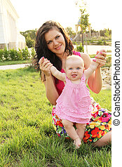 Happy Baby making first steps with mother help