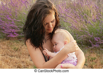 Mother rock a baby to sleep, outdoors portrait