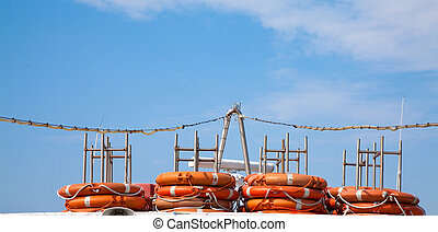 Lifejackets - Piled lifejackets with a blue sky