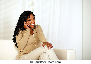 Young woman smiling at you while speaking on phone -...
