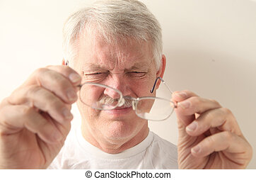 senior man with dirty glasses - an older man squints at his...