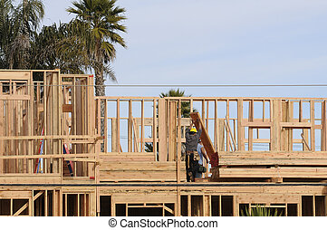 Carpenter raising wood - Hispanc construction worker raising...