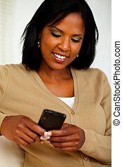 Charming black woman sending message by cellphone - Portrait...