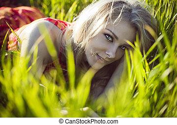 beautiful girl lies in a green grass