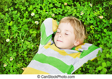 Little child sleeping outdoors on grass, hands behind head -...