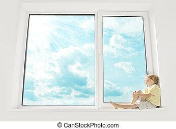 Child sitting on window, enjoying sunshine and dreaming. Big...