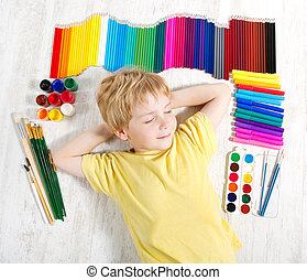Child dreaming lying next to pencils, brushes and paints.