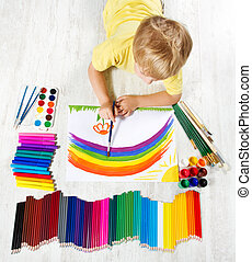 Child painting picture with brush in album