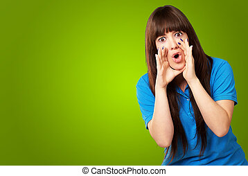 portrait of a teenager screaming on green background