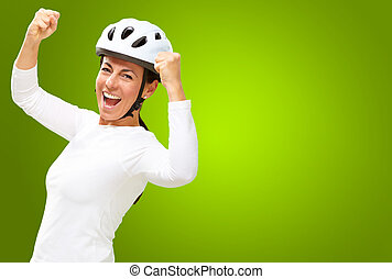 Woman wearing helmet cheering isolated on green background