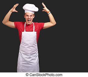 Angry Young Man Raising His Hand On Black Background