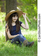Young fashion girl in white hat at green grass.