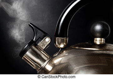 Tea kettle with boiling water on the black background
