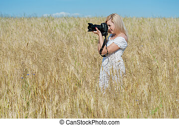 Beautiful woman take a photo with camera in a field -...