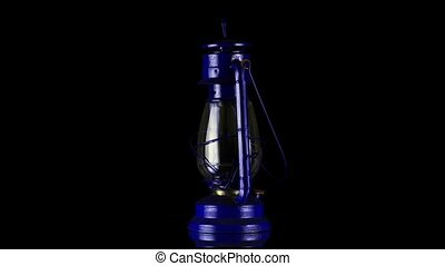 Old oil lamp rotating on black  background.