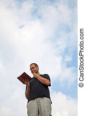 Young man staying with the Bible against blue sky