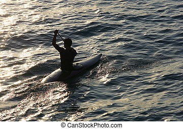 Silhouette of a man canoeing